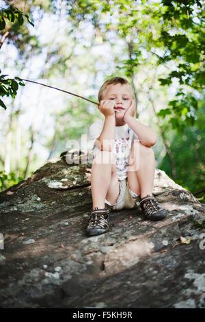 Sweden, Sodermanland, Strangnas, Portrait of boy (4-5) sitting on rock - Stock Photo