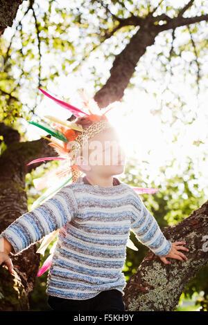 Sweden, Sodermanland, Strangnas, Boy (4-5) wearing plume in sunlight - Stock Photo