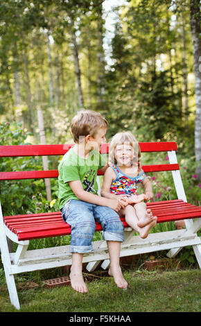 Sweden, Narke, Hallsberg, Boy (4-5) and girl (2-3) sitting on bench - Stock Photo
