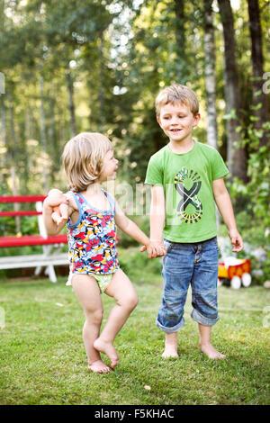 Sweden, Narke, Hallsberg, Boy (4-5) and girl (2-3) holding hands - Stock Photo