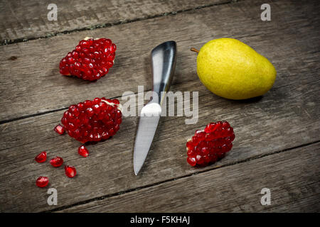 Ripe pomegranates with pear and knife on wooden background. - Stock Photo
