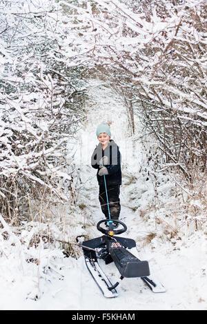 Sweden, Sodermanland, Strangnas, Boy (4-5) dragging sledge - Stock Photo