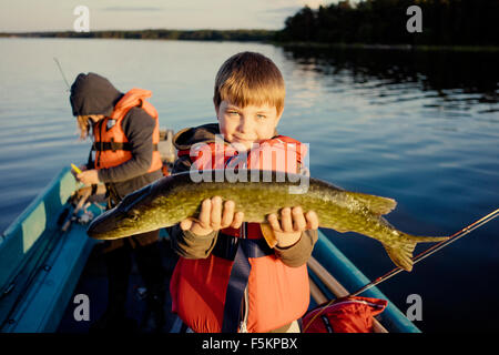 Sweden, Smaland, Tjust archipelago, Vastervik, Hasselo, Boy (10-11) on boat showing caught fish with girl in background - Stock Photo