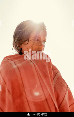 Sweden, Smaland, Tjust archipelago, Vastervik, Hasselo, Girl (8-9) wrapped in towel against sky - Stock Photo