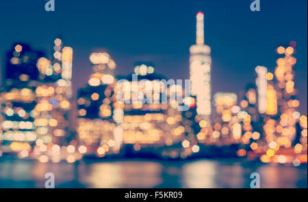 Vintage toned blurred Manhattan waterfront at night, New York City, USA. - Stock Photo