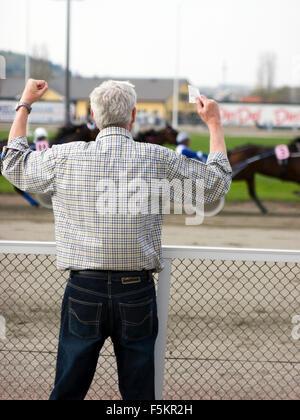 Sweden, Vastra Gotaland, Gothenburg, Man watching horse race - Stock Photo