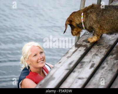 Sweden, Bohuslan, Tjorn, Woman smiling at dog on jetty - Stock Photo