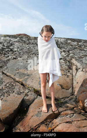 Sweden, Halland, Onsala, Girl (6-7) wrapped in towel, standing on rock - Stock Photo