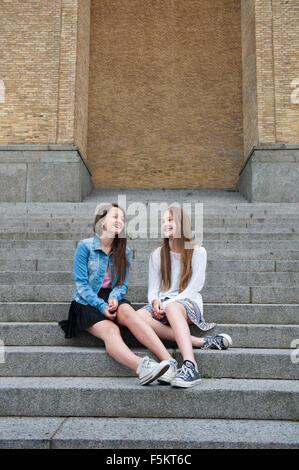 Sweden, Vastra Gotaland, Gothenburg, Gotaplatsen, Teenage girls (14-15) sitting on steps - Stock Photo