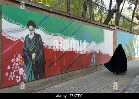 Tehran, Iran. 4th November, 2015.veiled Iranian woman, walks past a Ayatollah Khomeini's picture painted on a wall - Stock Photo