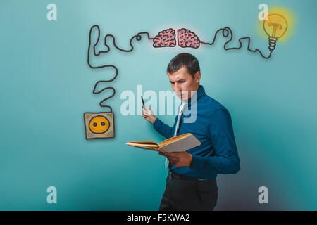 Male businessman reading a book charging cord plug wire igniter - Stock Photo