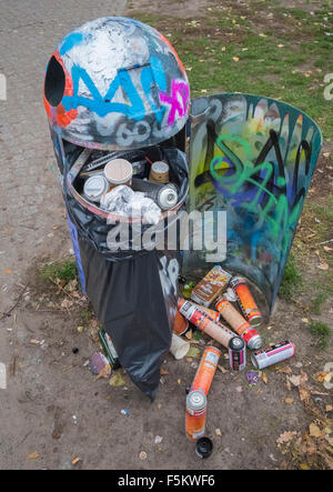 Used paint spray cans in refuse container - Stock Photo