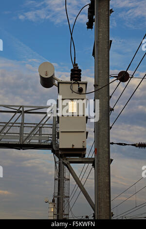 A pole mounted high voltage transformer wired up to the overhead line equipment that feeds trains on adjacent lines - Stock Photo