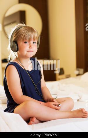 Turkey, Alanya, Portrait of blonde girl (4-5) wearing headphones - Stock Photo