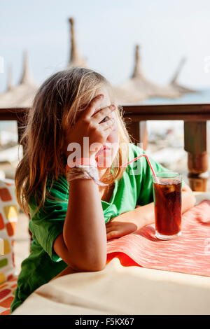 Turkey, Alanya, Girl (4-5) sitting at table and covering her face with hand - Stock Photo