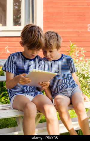 Sweden, Halsingland, Jarvso, Brothers (4-5, 6-7) using digital tablet - Stock Photo