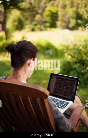 Sweden, Halsingland, Jarvso, Woman using laptop in garden - Stock Photo