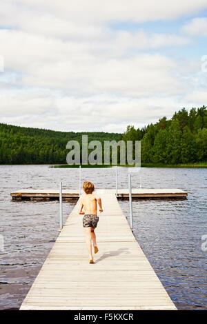 Sweden, Uppland, Runmaro, Barrskar, Rear view of boy (6-7) running on jetty - Stock Photo