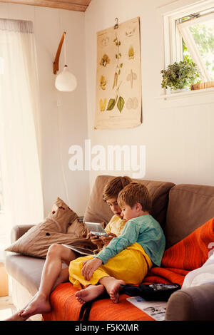 Sweden, Uppland, Runmaro, Barrskar, Brothers (4-5, 6-7) playing on game console on sofa - Stock Photo
