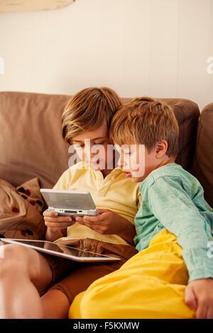 Sweden, Uppland, Runmaro, Barrskar, Brothers (4-5, 6-7) playing on game console - Stock Photo