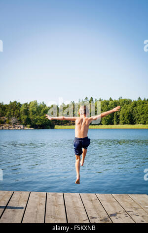Sweden, Uppland, Runmaro, Barrskar, Rear view of boy (6-7) jumping into water from jetty - Stock Photo