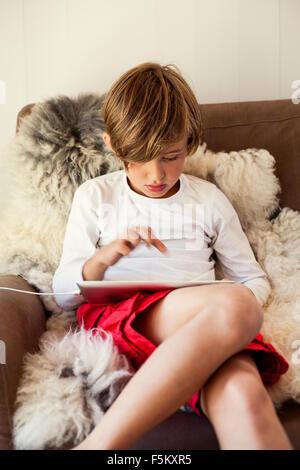 Sweden, Uppland, Runmaro, Barrskar, Boy (6-7) using digital tablet
