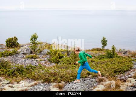 Sweden, Uppland, Runmaro, Barrskar, Boy (6-7) running by sea