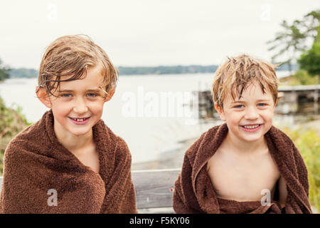 Sweden, Uppland, Runmaro, Barrskar, Portrait of two boys wrapped into towels - Stock Photo