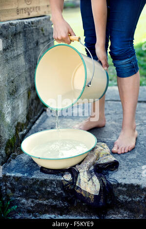 Sweden, Uppland, Woman pouring water into wash bowl - Stock Photo