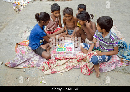 Children playing ludo game on footpath, kolkata, west bengal, india, asia - Stock Photo