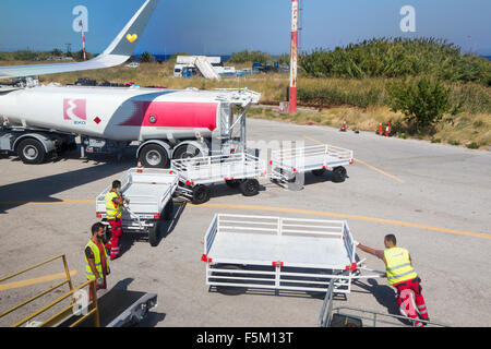 Baggage handlers and a refuelling tanker at Mytilene airport on Lesvos, Greece. - Stock Photo