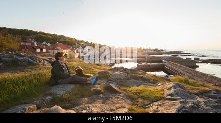 Denmark, Bornholm, Gudhjem, Mature woman with dog sitting on coastline - Stock Photo