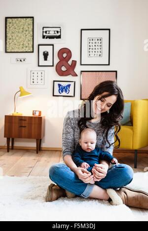 Mother with baby son on lap in living room - Stock Photo