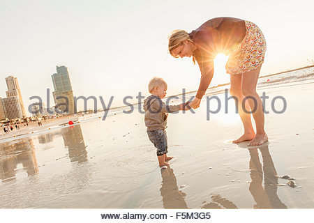 United Arab Emirates, Dubai, Woman with son (12-17 months) on beach at sunset - Stock Photo