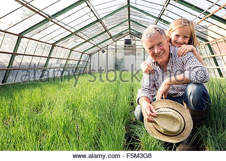 Granddaughter with hands on grandfather shoulders in hothouse full of chives, looking at camera smiling - Stock Photo