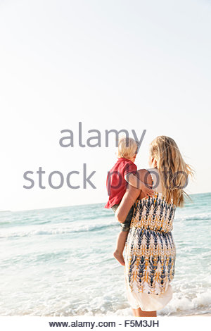 United Arab Emirates, Dubai, Woman carrying son (12-17 months) on beach - Stock Photo