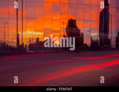 Highway traffic light trails and glass fronted office building at sunset - Stock Photo