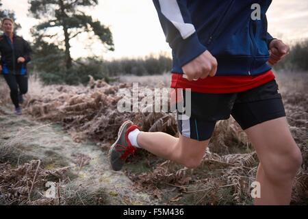 Cropped low angle view of mother and son jogging on frosty grassland - Stock Photo