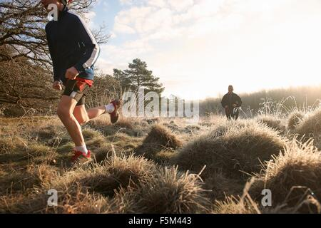 Low angle view of mother and son running on grassland - Stock Photo