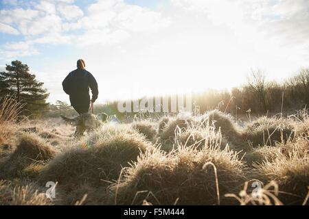 Low angle rear view of mature woman walking dog on grassland - Stock Photo