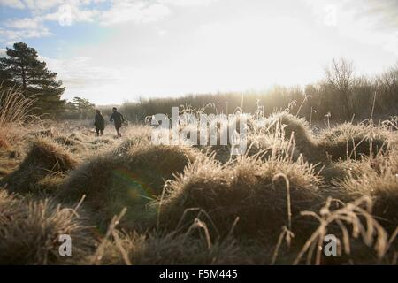 Rear angle view of mother and son running on grassland - Stock Photo
