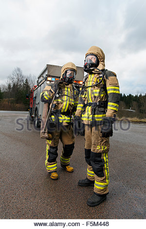 Sweden, Sodermanland, Tumba, Firefighters wearing gas mask standing on road - Stock Photo