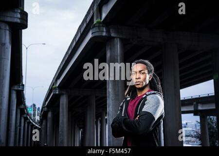 Portrait of male boxer with arms folded standing below urban flyover - Stock Photo