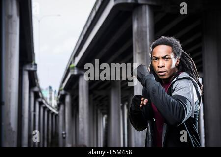 Portrait of male boxer with fists raised standing below urban flyover - Stock Photo