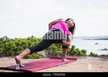 Woman practicing yoga pose on beach, Hawea Point, Maui, Hawaii, USA - Stock Photo