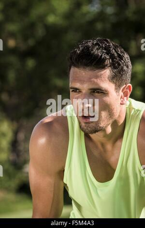 Portrait of sweaty young man training in park - Stock Photo
