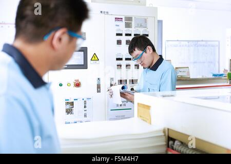 Colleagues at work in flexible electronics plant - Stock Photo
