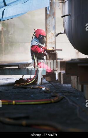 Worker sandblasting boat hull in shipyard - Stock Photo