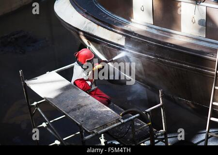 Worker cleaning hull of boat with high pressure hose in shipyard - Stock Photo