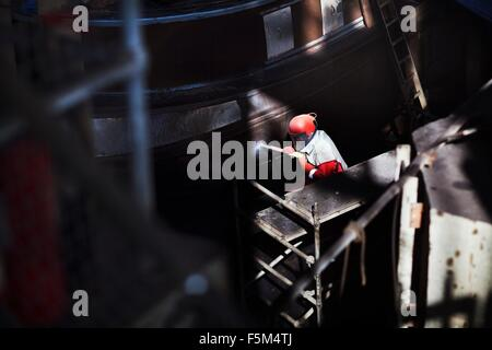 Worker cleaning boat with high pressure hose in shipyard - Stock Photo